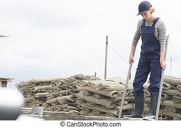 female worker with oysters in metal bag on farm