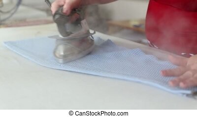 Female worker work with professional ironing appliance at...