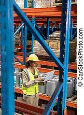 Female worker working on laptop in warehouse