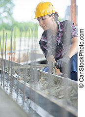 female worker working on the foundations of a construction site