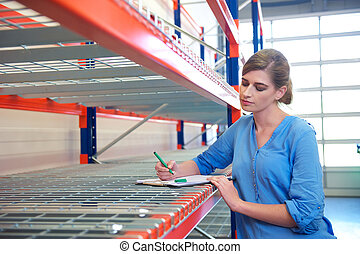 Female worker writing inventory at delivery depot warehouse