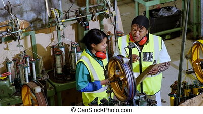 Female workers discussing over clipboard 4k - Female workers...