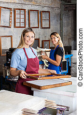 Portrait of smiling female workers making papers together in factory