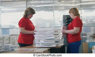 Female workers sorting a paper stacks in the typography,...