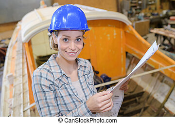 female working at a boat workshop