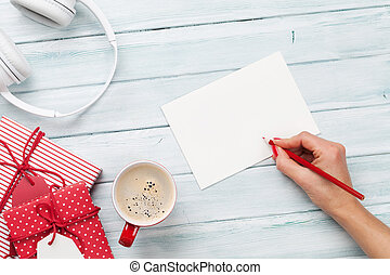 Female writing greeting card and wrapping christmas gifts