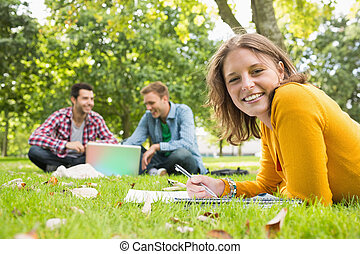 Female writing notes with students using laptop at park -...