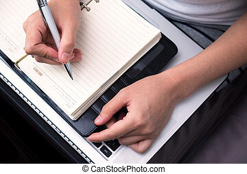 female writing on notebook