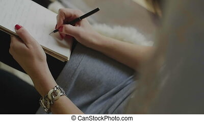 Female Writing on Notepad With a Pen. Woman sitting at the...