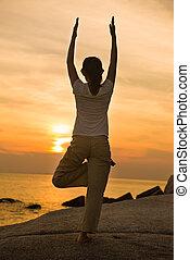 female yoga silhouette on beautiful beach during sunset