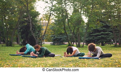 Female yoga students are doing stretching exercises with...