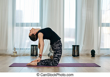 yoga teacher female standing in ustrasana camel posture