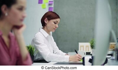 Female young businesswoman or architect in office, working....