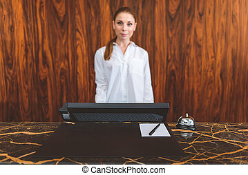 Female young receptionist behind desk