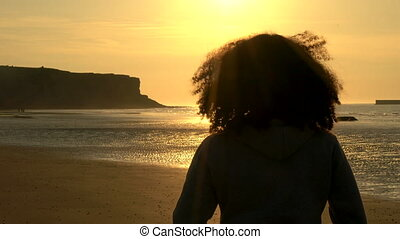 female young woman with curly hair standing on a beach...