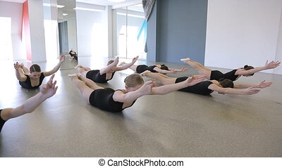 Females are doing stretching exercises lying on floor.