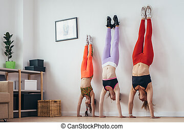 Females doing handstand pose near wall. Mother and daughters...