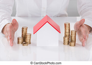 Female's Hand Protecting House Model And Stacked Coins