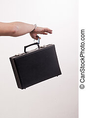 females hand with handcuff and a suitcase