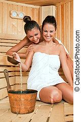 females joy sauna - Two beautiful happy females in sauna,...