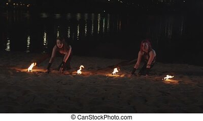 Females jugglers raising lit torches lying on sand