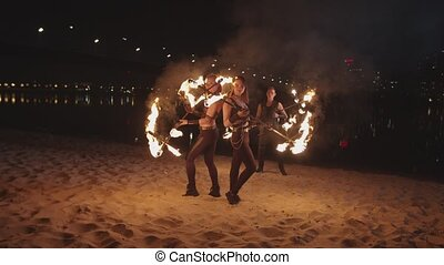Females performing skill of spinning flaming staves -...