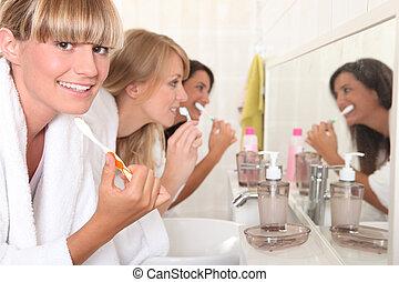 Females roommates brushing teeth
