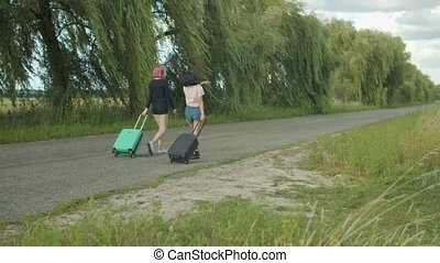 Females with suitcases travelling in countryside - Rear view...