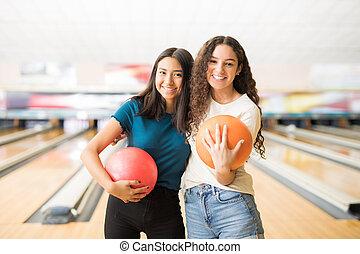 femininas, amigos, com, bolas boliche, pendurando, em, ruela