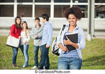 femininas, livros, estudante universitário, segurando, campus