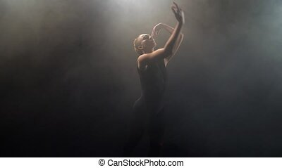 Top view of graceful young dancer in black leotard performing elegant dance elements in twilight of smoky studio. Tender woman artist dancing modern contemp in puffs of smoke against black background