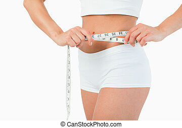 Feminine body with a measuring tape against a white...