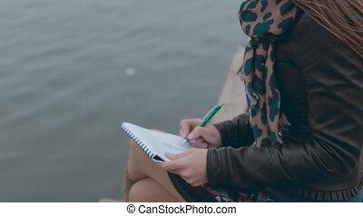 Feminine girl sitting at berth near the sea and drawing...