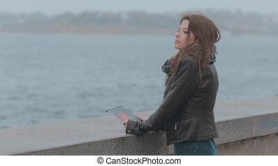 Feminine girl standing on the seafront promenade, the...