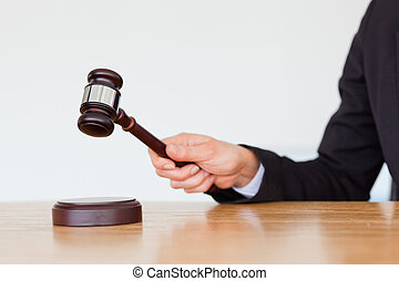 Feminine hand knocking a gavel against a white background