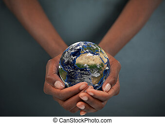 Feminine hands holding the Earth against a dark background