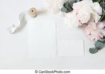 Feminine wedding, birthday table composition with floral bouquet. White and pink peonies flowers, eucalyptus and silk ribbon. Blank cotton paper card mockups, invitations. Flat lay, top view.