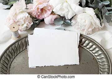 Feminine wedding or birthday table composition with floral bouquet. White and pink peonies flowers, eucalyptus, old vintage silver tray and silk ribbons. Blank cotton paper cards, invitations.