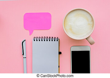 feminini desk workspace with smartphone, blank notepad, pen, cup of coffee on pink background. flat lay, top view.