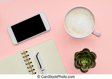 feminini desk workspace with smartphone, blank notepad, pen, cup of coffee on pink background. flat lay, top view