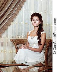 Femininity. Brown Hair Woman Bride in Wedding Dress sitting. Classic Romantic Interior