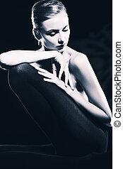 femininity - Elegant naked young woman posing over black...