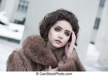 Femininity. Portrait of Sophisticated Young Brunette in Brown Fur Coat Outdoors