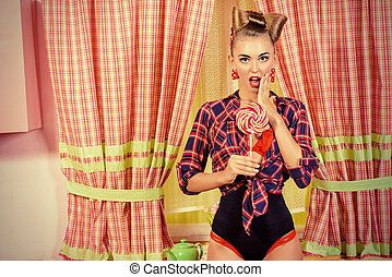 Pretty pin-up girl posing on a pink kitchen with a lollipop. Retro style. Fashion.