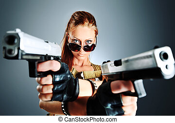 feminism - Shot of a sexy military woman posing with guns.
