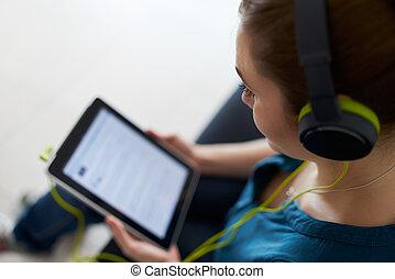 femme, à, vert, écouteurs, écoute, podcast, musique, pc tablette