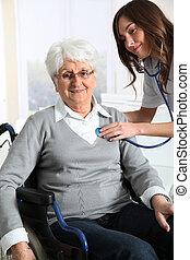 femme âgée, dans, fauteuil roulant, à, infirmière, chez soi