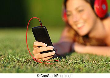 femme, écouteurs, haut, téléphone, tenir fermeture, intelligent