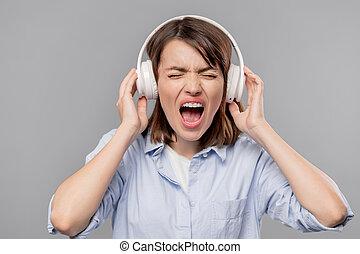 femme, écouteurs, jeune, loudly, furieux, crier