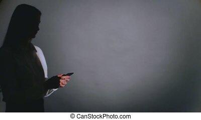 femme, élégant, mobile, jeune, téléphone, conversation, noir, contre, fond, ombre